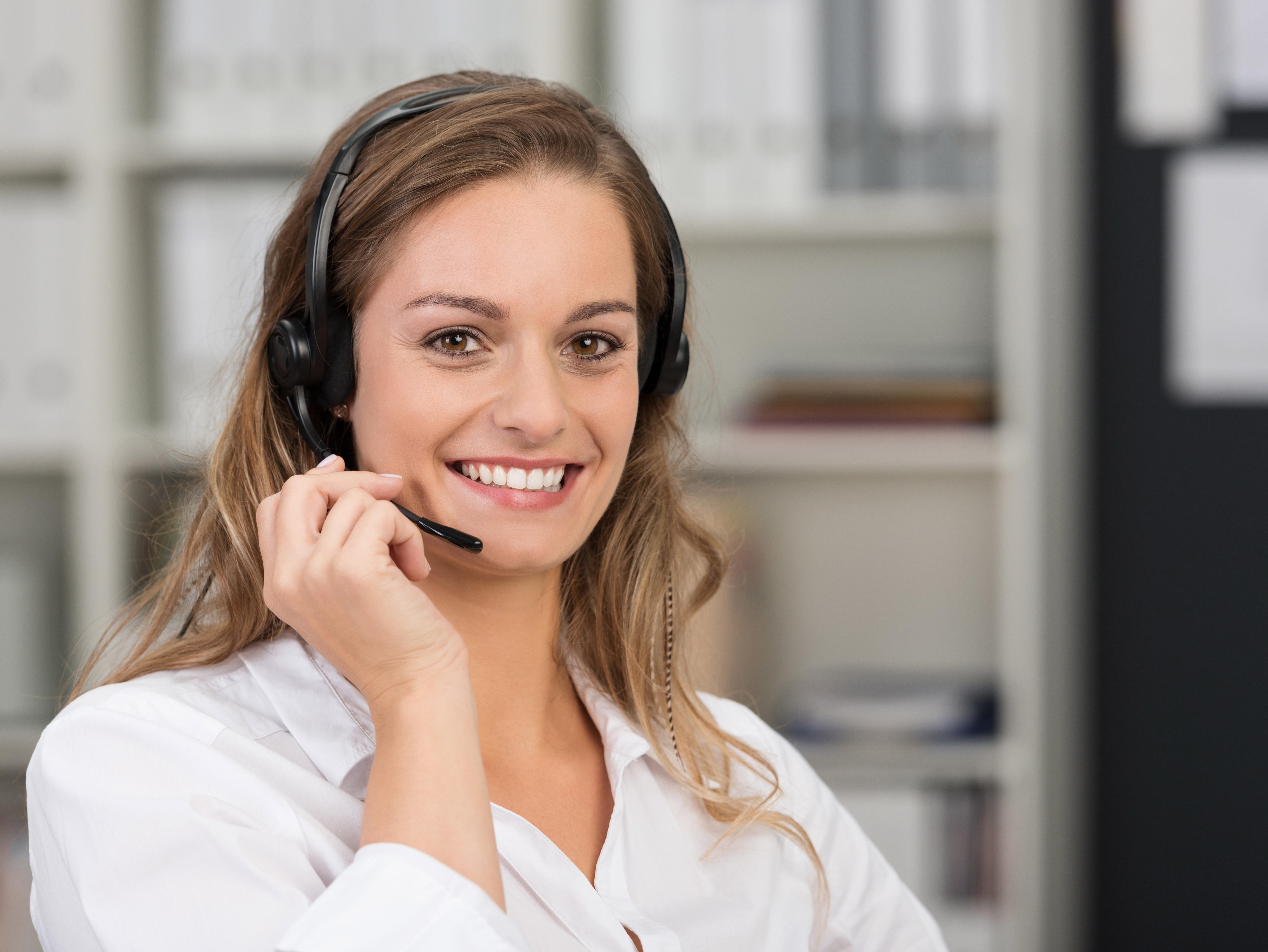 Lächelnde Frau am Schreibtisch mit Headset